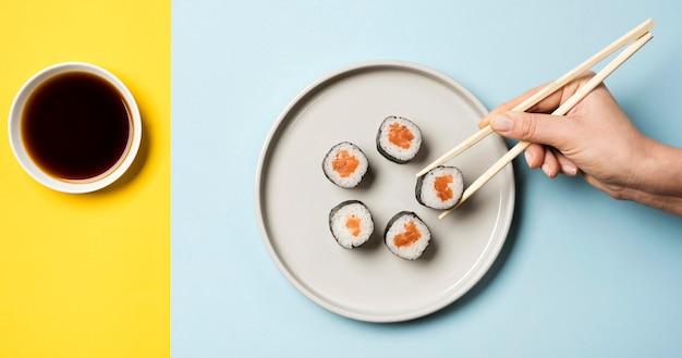 Prato de sushi japonês com pauzinhos e molho de soja