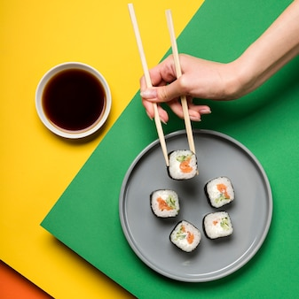 Prato de sushi japonês e mão segurando os pauzinhos