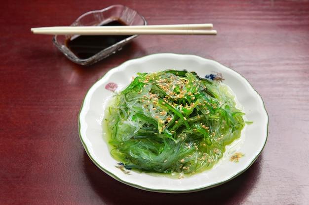 Prato de sushi japonês, na mesa de madeira.