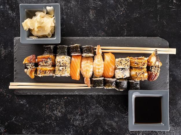 Prato de sushi na pedra escura ao lado de pauzinhos em fundo preto no estúdio. comida asiática saudável