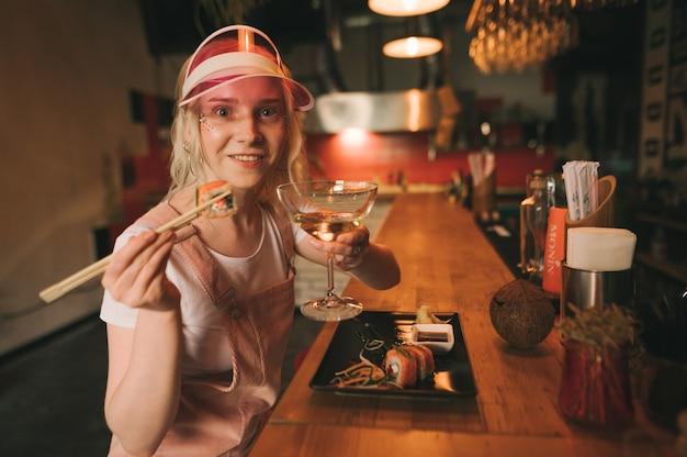 Prato de sushi rola em restaurante com uma mulher segurando os pauzinhos