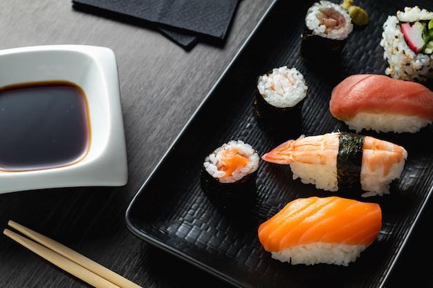 Prato de sushi variado na mesa de madeira