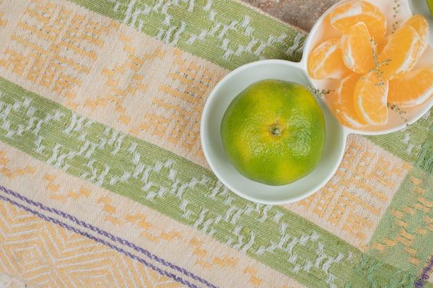 Prato de tangerinas frescas e segmentos na toalha de mesa.