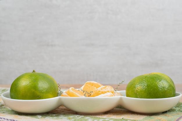 Prato de tangerinas frescas na mesa de mármore com toalha de mesa.