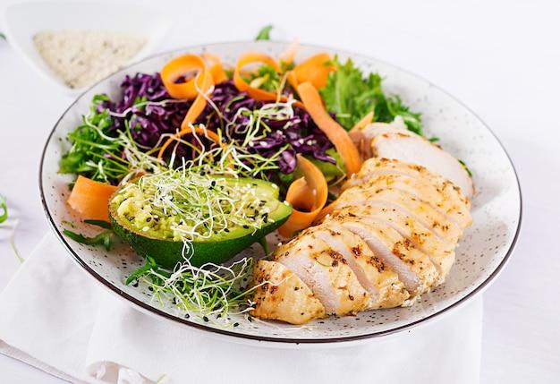 Prato de tigela de buda com filé de frango, abacate, couve roxa, cenoura, salada de alface fresca e gergelim.