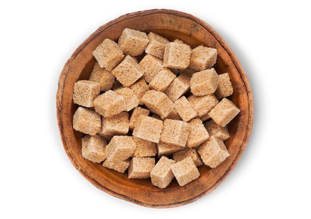 Prato de tigela de madeira de cubos de açúcar mascavo natural em branco.