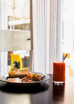 Prato de torrada; salada; ovos fritos; bacon com copo de suco na mesa preta perto da janela