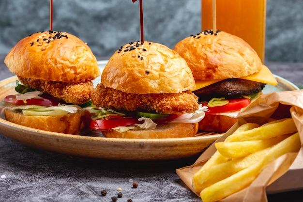 Prato de três mini hambúrgueres servido com batatas fritas em caixa de papel