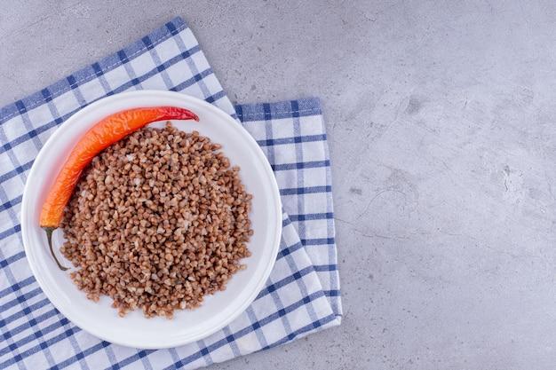 Prato de trigo mourisco cozido com pimenta em uma toalha sobre fundo de mármore. foto de alta qualidade