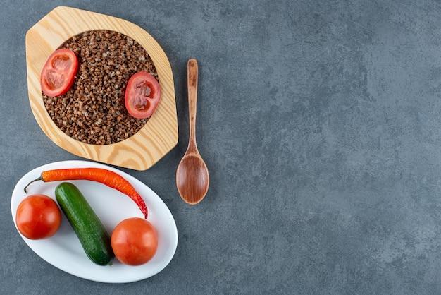 Prato de trigo sarraceno cozido com rodelas de tomate ao lado de uma colher e um prato de tomate