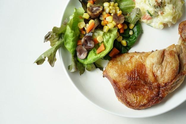 Prato de um delicioso bife de coxas de frango grelhado com vegetais e salada de batata no fundo branco