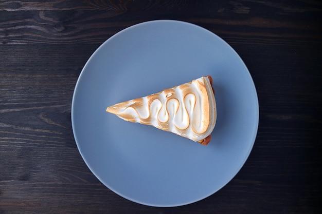 Prato de uma fatia de torta de limão e merengue deliciosa na superfície de madeira preta