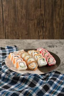 Prato de vários deliciosos rolos de sushi na mesa de mármore