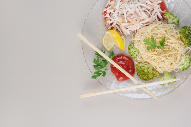 Prato de vidro com espaguete, frango e vegetais na superfície branca