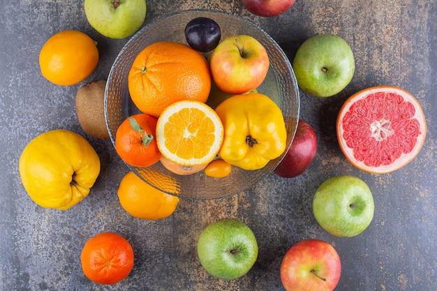 Prato de vidro com frutas frescas em cima de muitas frutas.