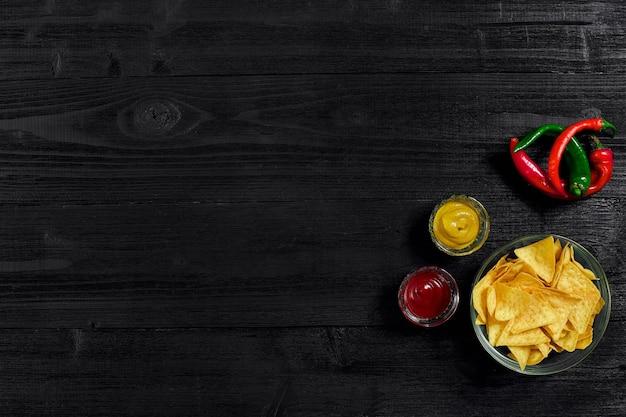Prato de vidro com nachos de salgadinhos de milho e molho de tomate em uma mesa de madeira preta com vista para texto