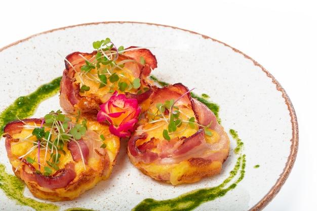 Prato de vieiras de bacon embrulhado em linhas puras em um prato de cor clara