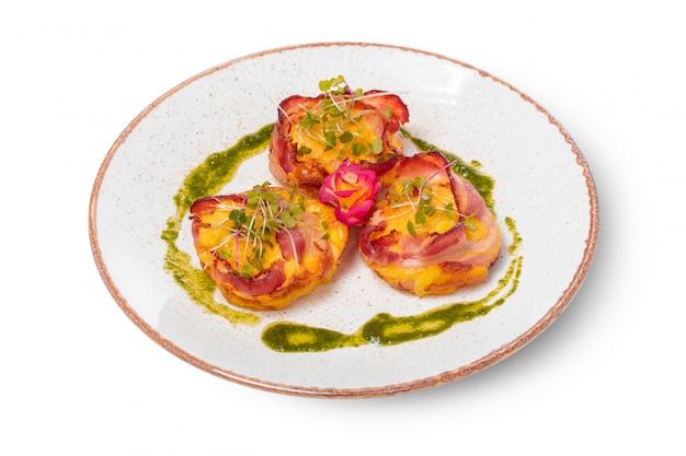 Prato de vieiras embrulhadas em bacon em linhas puras em um prato de cor clara