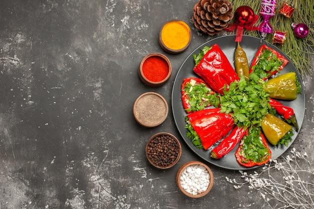 Prato de visão de close-up superior de pimentas, pimentões e ervas no prato, cones de especiarias, brinquedos para árvores de natal