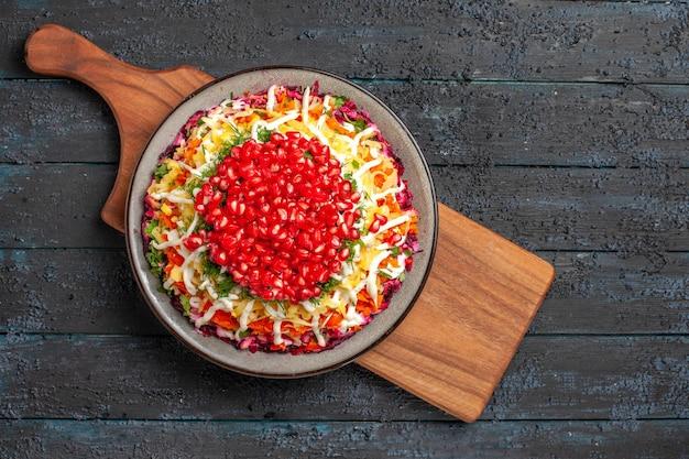 Prato de vista de cima em close-up a bordo de romãs apetitosas no prato na tábua de corte