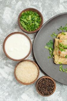 Prato de vista de cima em close-up de tigelas de repolho recheado de ervas, arroz de creme azedo e pimenta do reino ao lado do prato cinza de repolho recheado na mesa