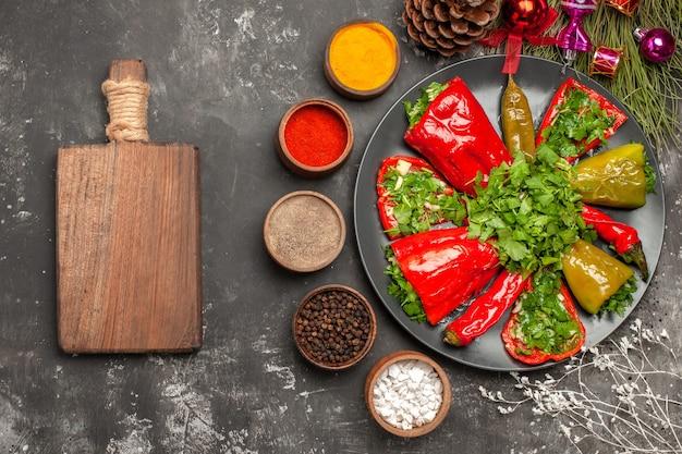 Prato de vista de close-up superior de pimentas, pimentas e ervas, tábua de madeira, cones de especiarias, brinquedos de natal