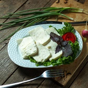 Prato de vista superior com queijo com cebolinha e manjericão