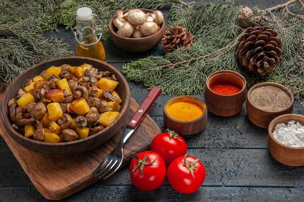 Prato de vista superior do prato de comida de batatas e cogumelos na tábua de cortar ao lado do garfo três tomates e especiarias coloridas sob a tigela de óleo de cogumelos brancos e ramos de abeto