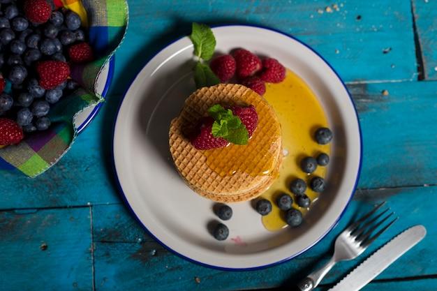 Prato de waffle holandês com framboesas, mirtilos e mel sobre fundo azul de madeira. imagem isolada tiro aéreo. conceito de pequeno-almoço.