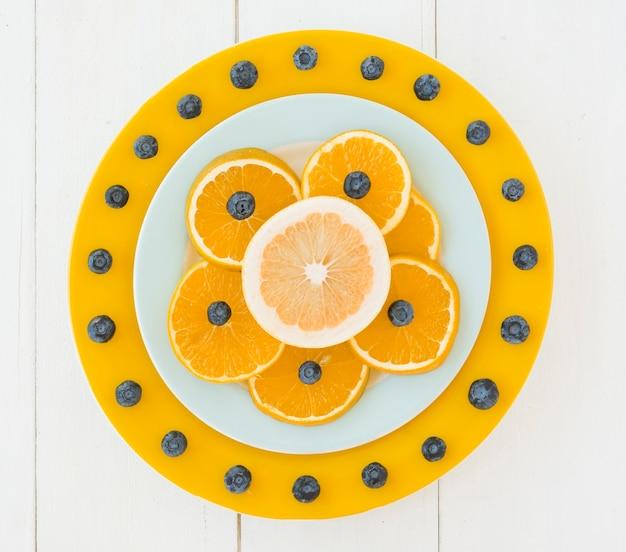 Prato decorado com mirtilos e fatias de laranja na mesa de madeira