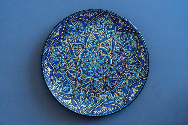 Prato decorativo de cerâmica nas cores azul e dourado, pintado, close-up. prato decorativo de porcelana pintado com tintas acrílicas, trabalho manual