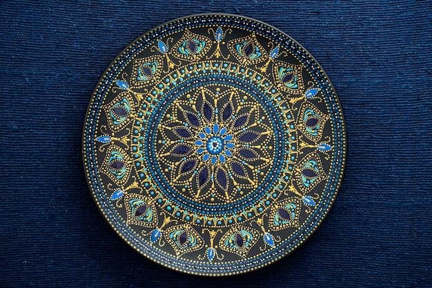 Prato decorativo de cerâmica nas cores preto, azul e dourado