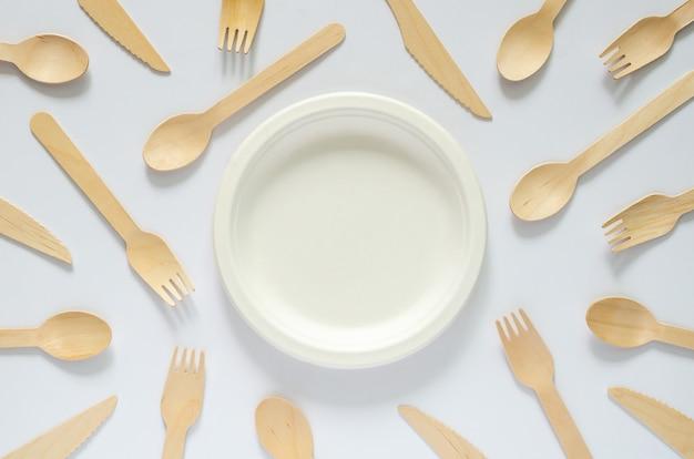 Prato descartável branco compostável com garfo e colher no fundo branco para o conceito do dia do meio ambiente mundial