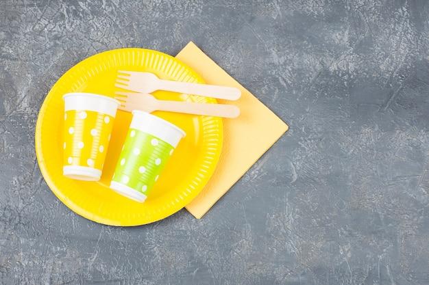 Prato descartável, garfos, copos descartáveis e um guardanapo