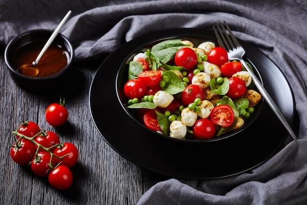 Prato dietético: salada caprese italiana com espinafre baby, tomate cereja, bolinhas de mussarela, vinagre balsâmico e molho de azeite em um prato preto, garfo em uma mesa de madeira escura, close-up