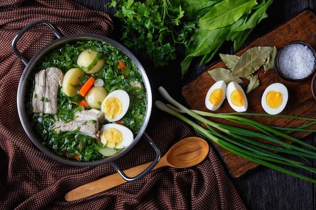 Prato do leste europeu: borscht de azeda verde de azeda fresca, cebola verde com costela de porco, batata jovem, cenoura e ovos cozidos servidos em uma panela em uma mesa de madeira com ingredientes, postura plana