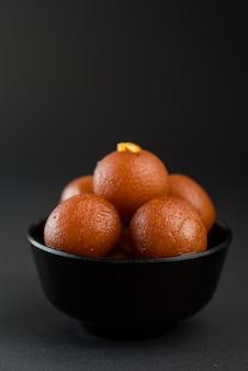 Prato doce gulab jamun em uma tigela preta