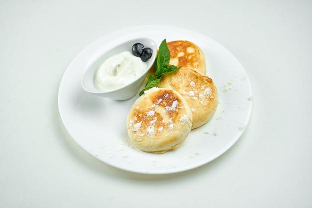 Prato doce ucraniano - panquecas de queijo cottage com creme de leite em um prato branco sobre uma superfície branca. doce syrniki