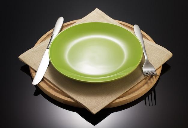 Prato e garfo com faca em pano de guardanapo em fundo preto