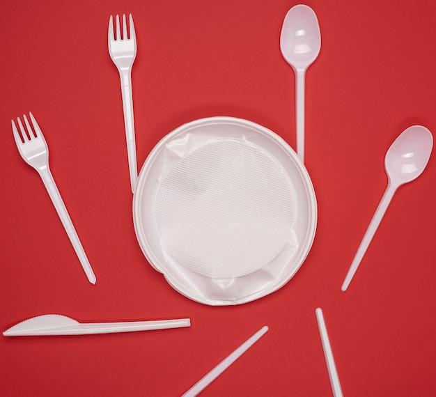 Prato e pilha de garfos e colheres de plástico