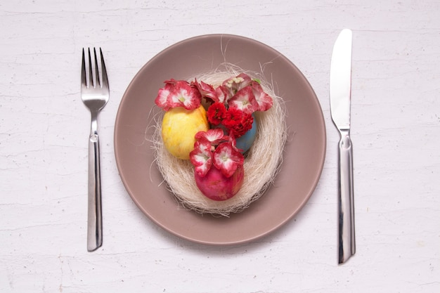 Prato e talheres com ovos coloridos, ninho e flores
