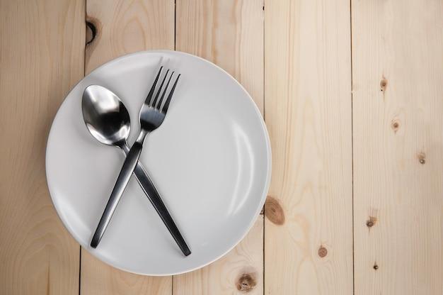 Prato e talheres na mesa de madeira
