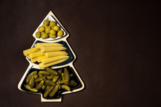 Prato em forma de árvore de natal com legumes em conserva em um fundo marrom. um prato de pepinos, milho e azeitonas no natal.