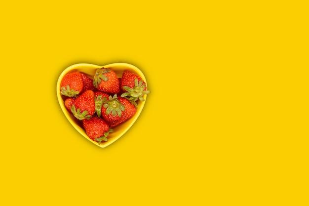 Prato em forma de coração amarelo com morangos frescos em um fundo amarelo.