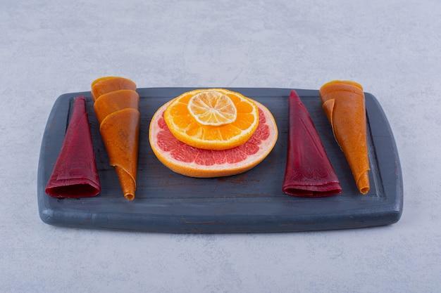 Prato escuro de deliciosas polpas de frutas secas e toranja na mesa de pedra.