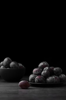 Prato escuro e tigela com ameixas em um fundo escuro