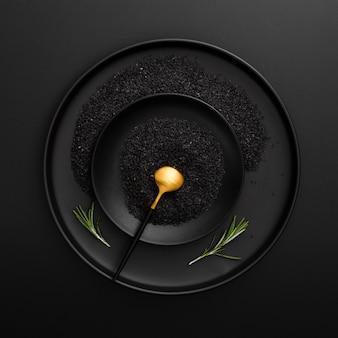Prato escuro e tigela com sementes de papoila em um fundo preto