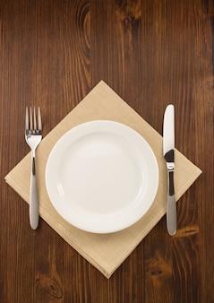 Prato, faca e garfo em fundo de madeira