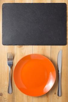 Prato, faca e garfo no fundo da mesa da prancha de madeira rústica, vista superior