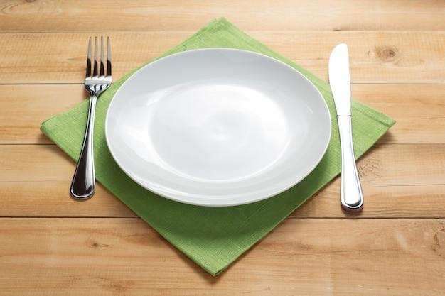 Prato, faca e garfo no fundo da mesa da prancha de madeira rústica